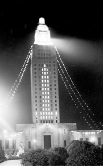 The tower light in the Louisiana State Capitol shines on the statue of Huey Long.