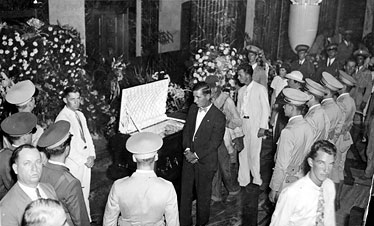 Mourners process by Huey Long's casket lying in state at the Louisiana State Capitol