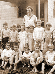 Teacher and students outside their one-room schoolhouse. Many poor families had to choose between buying their children shoes or school books.