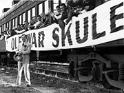 Huey Long standing in front of a train of Louisiana State University students on their way to a football game. 'Ole War Skule' is a reference to LSU's founding as a military academy after the Civil War.