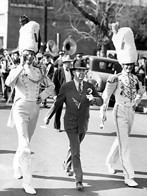 Huey Long marches with the Louisiana State University band. Long's first step to generate excitement for LSU was to quadruple the size of the marching band.