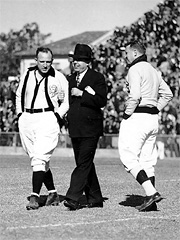 Huey Long on the gridiron with referees before a Louisiana State University football game.